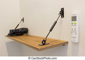 wooden shelf with hair dryer and remote control of the air condition on the wall