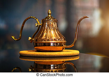 Copper kettle put on table and blurred background. - One...