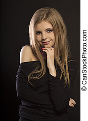 Smiling blonde woman with perfect makeup posing at studio -...