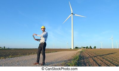 The engineer finishes work and leaves, looks at the windmills, holds a laptop in his hand.