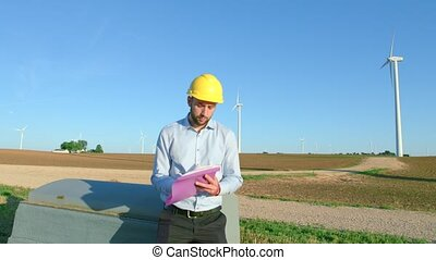 The engineer sits on the background of the windmills and...