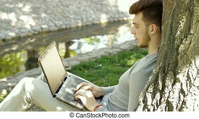 handsome guy working with a laptop under a tree in the Park
