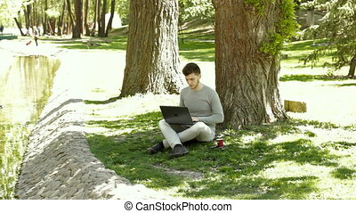 student doing homework on a computer in the park under a tree and drinks coffee