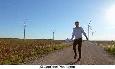 Engineer dances on windmills background.