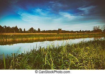 Rural summer sunset landscape with river and dramatic...