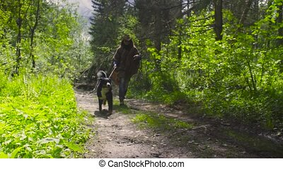 Young woman running with the dog in the forest - Young woman...