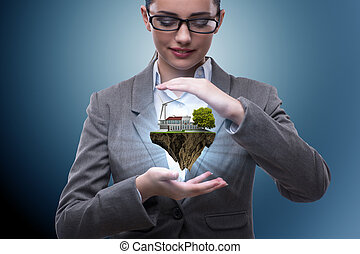 Businesswoman holding flying island in eco concept