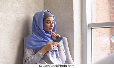 Muslim girl is holding a modern mobile phone. Beautiful young woman in hijab