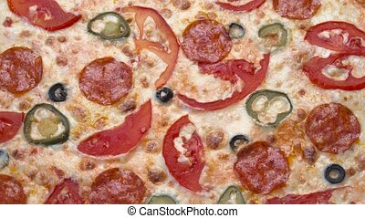 Large pizza with tomatoes and hot pepper spinning in a...