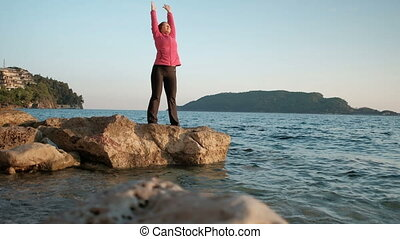 At sunset, a woman meditates by the lake standing on a rock....