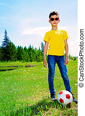 play football in a park - Happy boy plays football in the...