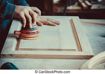 Close-up of carpenter using sander for wood furniture. Soft...