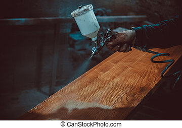 Master painter in a factory - industrial painting wood with...
