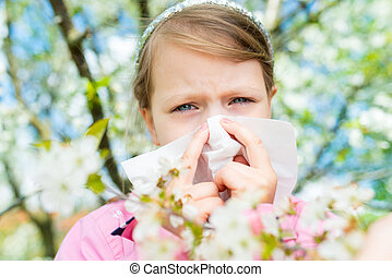 Allergy. Little girl is blowing her nose near spring tree in bloom - sneezing girl. Child with a handkerchief