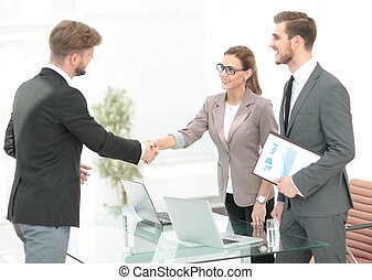 Business people closing a deal and handshaking at the office...