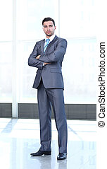 Full length of successful mature business man with crossed...