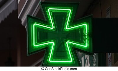 Green pharmacy sign illuminated at night and blinking