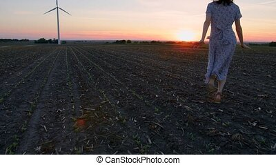 Beautiful young woman enjoying nature at sunset against the background of a windmill.