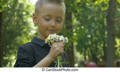 Young child smelling summer flowers and feeling nose...