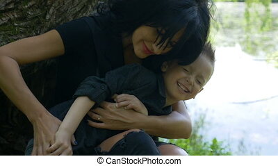 Attractive woman hugging and caressing her child sitting near a lake in the park