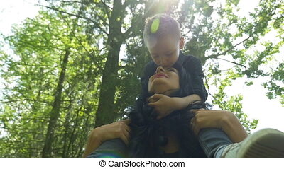 Young beautiful mom carrying her happy son on her shoulders...