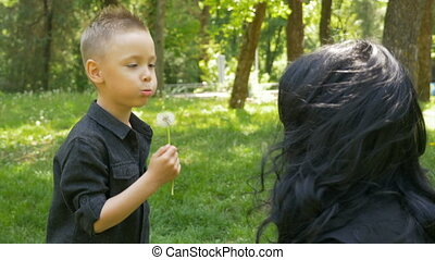 Kid blowing dandelion green seeds in front of his mother and hugging her in park