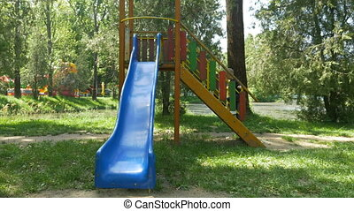 Young happy boy playing in public park on a slide