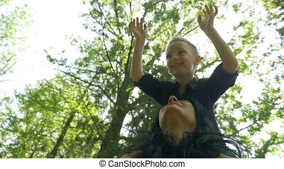 Child smiling while standing on mother shoulders enjoying his recreational time raising hands in the air