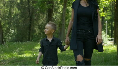 Smiling joyful baby boy walking in the park with his mother holding her hand and feeling happy