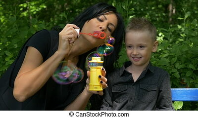 Mother entertaining and teaching her boy making iridescent...