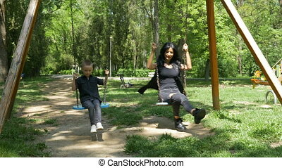 Mother and child on a swing set having fun in the park on a...