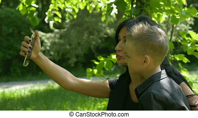 Mommy taking a selfie while being kissed by her child to...