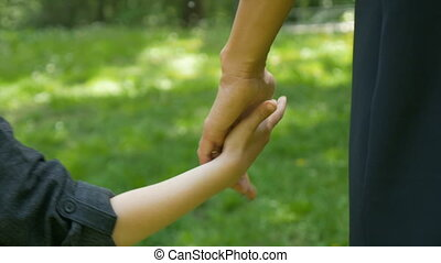 Mom and kid walking together holding hands in the park