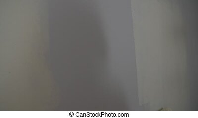 Painting out a bare wall with a paint roller with white...