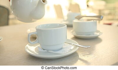 Someone pours tea from a porcelain white teapot into a white...