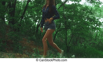young brunette in blue shirt and jeans short walks at the...