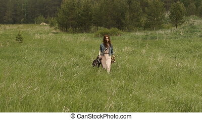 Woman walking on field with guitar