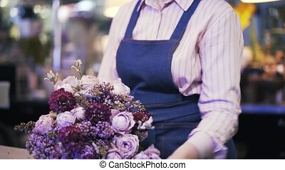 Side view of a woman florist making a purple bouquet and...