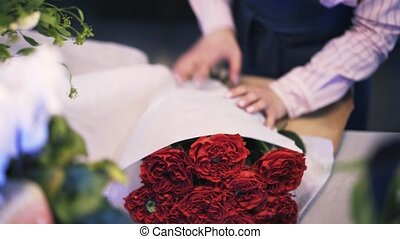 Woman working in a florist shop wrapping red roses in a white paper