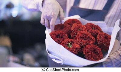 Woman working as a florist adjusting a red rose bouquet