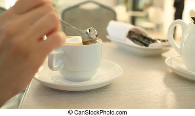 A child drinks hot tea with a spoon in a cafe.