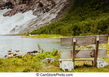 wooden bench at lake in mountain area