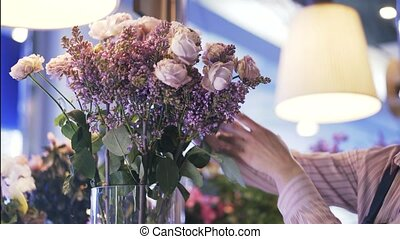 Florist shop employee putting pink and white flowers in a vase