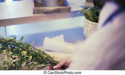 Side view of a saleswoman wrapping flowers in a florist shop...
