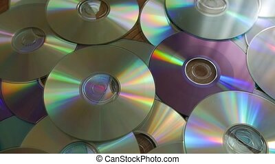 Optical Discs falling onto pile of DVDs or CDs.