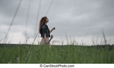 Woman carrying guitar on field