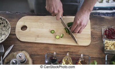 Top view of a chef cutting a cucumber on a wooden board in a cafe