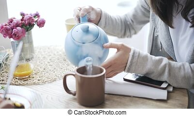 Pan shot of a woman pouring tea for her friend eating vegetables in a cafe