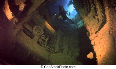 Cameraman diver swimming on background of ship wreck underwater in Red sea.