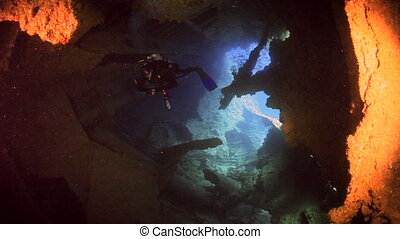 Cameraman diver swimming in ship wreck underwater of Red sea.
